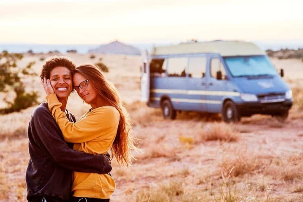 Abi and Nat lovingly embrace one another with the van in the background.